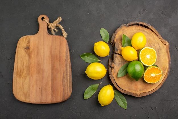 Vista dall'alto limoni freschi aspri con foglie sul tavolo scuro giallo frutta lime agrumi