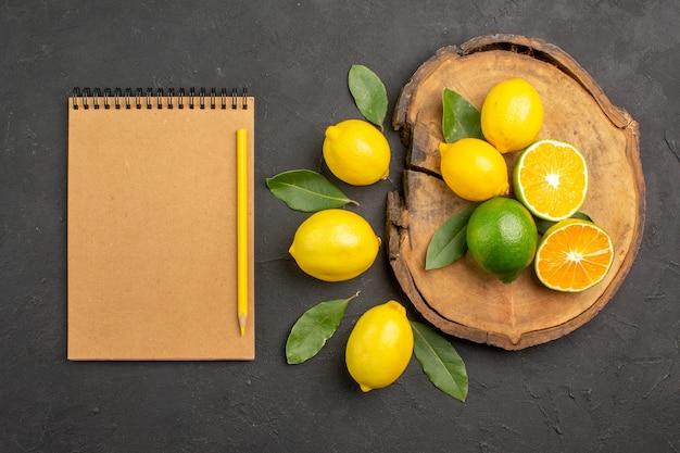 暗いテーブルに葉を持つ新鮮なサワーレモンの上面図黄色のフルーツライム柑橘類