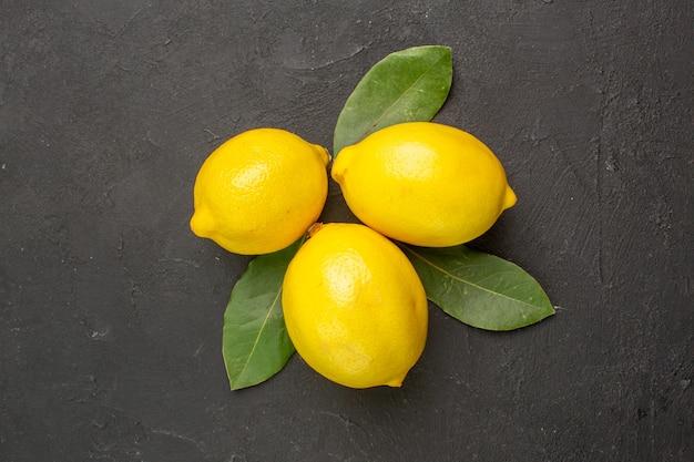 暗いテーブルに葉を持つ新鮮な酸っぱいレモンの上面図柑橘類のライムの黄色い果実