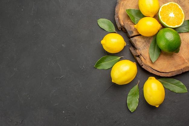 Вид сверху свежие кислые лимоны с листьями на темном столе, фрукты, лайм, желтые цитрусовые