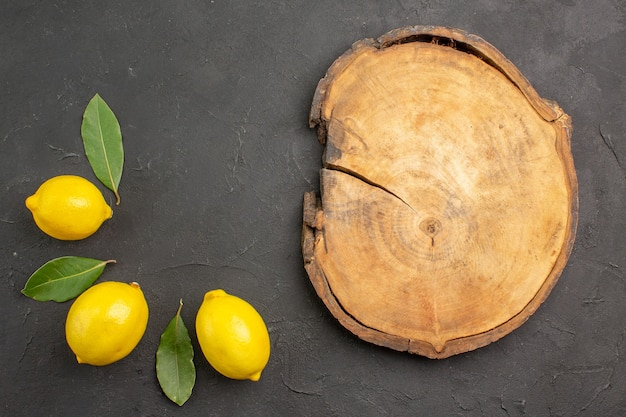 Вид сверху свежие кислые лимоны с листьями на темном столе фруктов, лайма, желтых цитрусовых