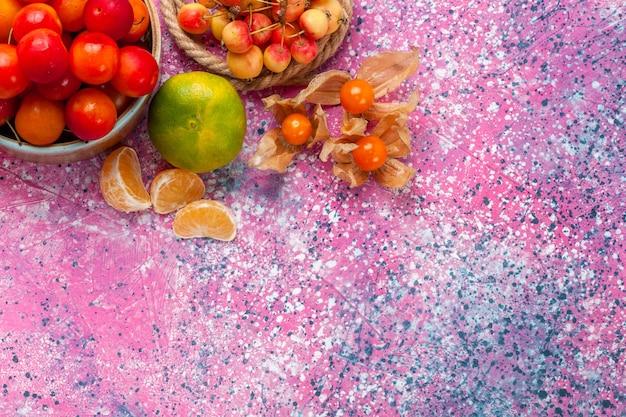 Вид сверху свежие кислые сливы спелые фрукты внутри маленькой тарелки на светло-розовом столе.