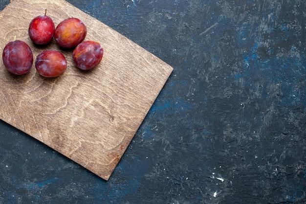 Vista dall'alto di prugne fresche acide intere morbide e succose su fondo scuro, frutta fresca