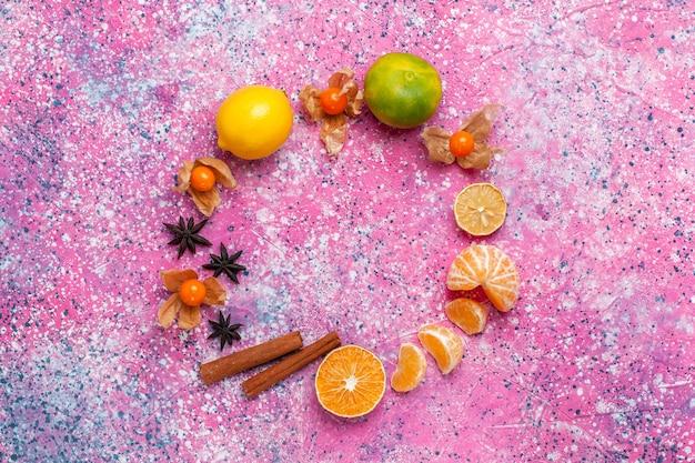 淡いピンクの背景にレモンとシナモンを添えた新鮮な酸っぱいみかんの上面図。
