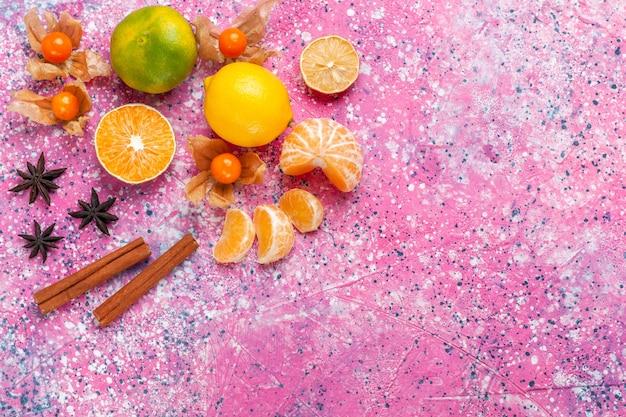ピンクの背景にレモンとシナモンと新鮮な酸っぱいみかんの上面図。