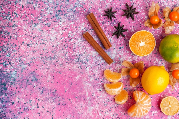 Top view fresh sour tangerines with lemons and cinnamon on the light pink background.