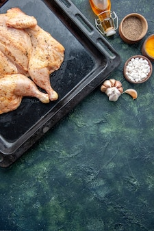 Top view fresh spiced chicken with seasonings on dark-blue background food spice pepper dish dinner meat color salt baking