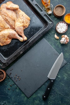 Vista dall'alto pollo speziato fresco con condimenti su sfondo blu scuro cibo spezie pepe piatto cena carne colore sale