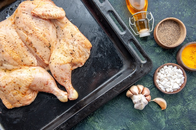 Top view fresh spiced chicken with seasonings on a dark-blue table food spice pepper dish dinner meat color salt baking