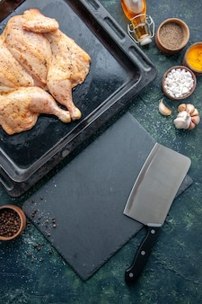 Вид сверху свежая пряная курица с приправами на темно-синем фоне еда специи перец блюдо ужин мясо цвета выпечка