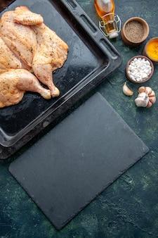 Вид сверху свежая пряная курица с приправами на темно-синем фоне еда специи перец блюдо мясо цвет соль выпечка