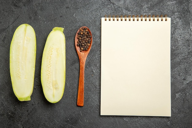 Top view of fresh squashes with notepad on grey surface