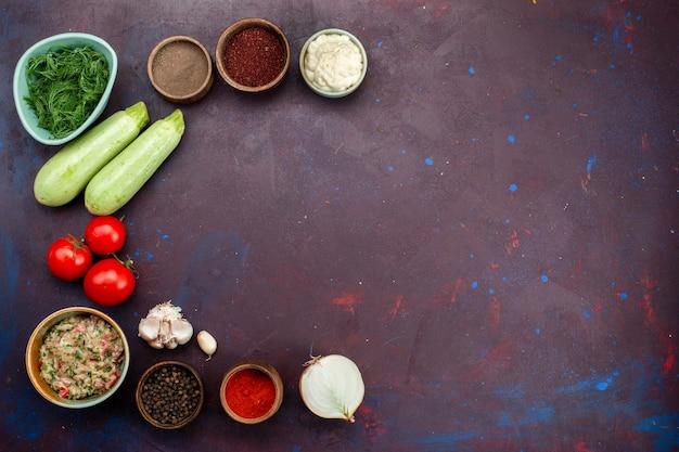 Vista dall'alto zucche fresche con pomodori verdi carne e condimenti sulla scrivania scura.
