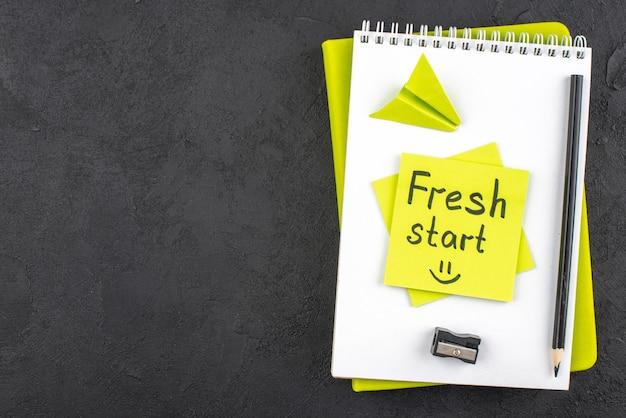 Vista dall'alto nuovo inizio scritto su una nota adesiva gialla sul blocco note matita nera e temperamatite su sfondo nero con spazio libero