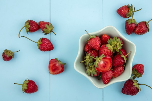 Top view of fresh strawberries on a bowl with strawberries isolated on a blue background