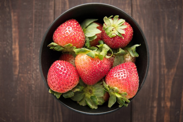 Top view fresh strawberries in a bowl on wood