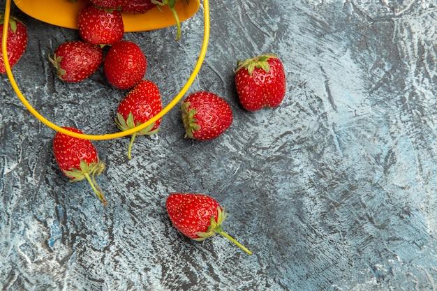 Вид сверху свежей клубники внутри корзины на темно-светлом столе, цвет ягодных фруктов, витамин