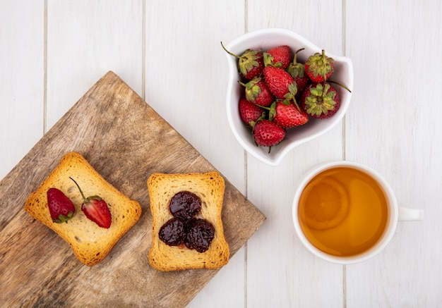 Top view of fresh strawberries on a white bowl with toasted slices of bread on a wooden kitchen board on a white wooden background