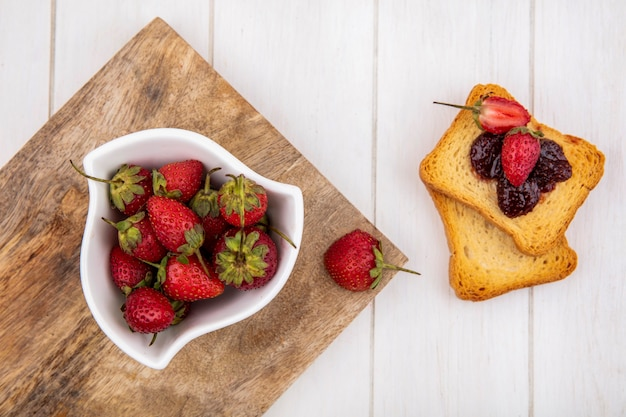 Top view of fresh strawberries on a white bowl on a wooden kitchen board with toasted slices of bread on a white wooden background