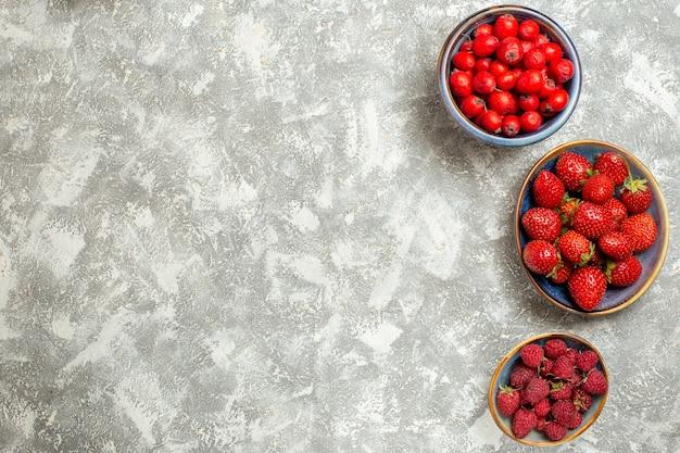 Vista dall'alto fragole fresche con frutti di bosco su sfondo bianco