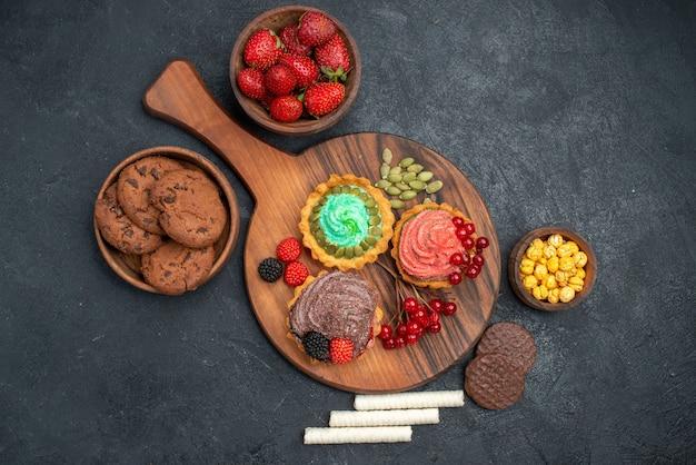 Вид сверху свежей клубники с печеньем и пирожными на темном столе сахарного печенья