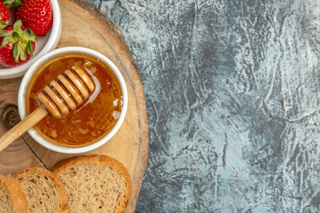 暗い表面にパンと蜂蜜を添えた新鮮なイチゴの上面図フルーツの甘いゼリー