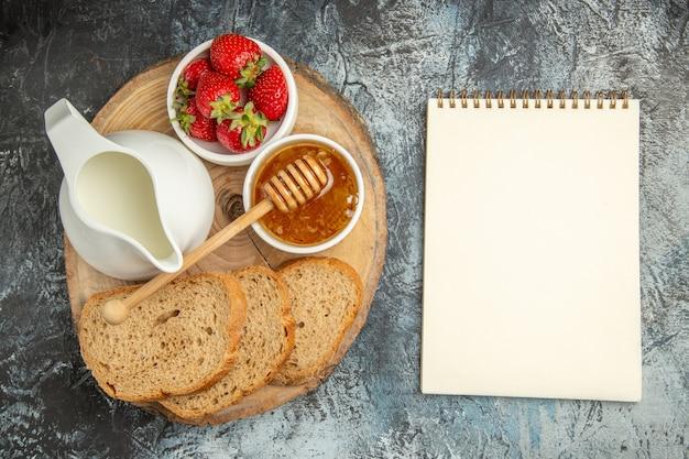 Vista dall'alto fragole fresche con pane e miele sulla gelatina dolce di frutta superficie scura