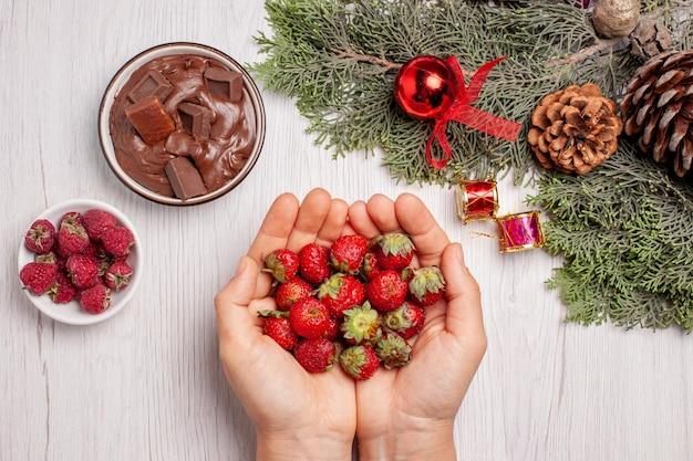 Vista dall'alto di fragole fresche con cioccolato sul tavolo bianco