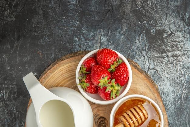 暗い表面の食品フルーツ甘いゼリーに蜂蜜とパンと新鮮なイチゴの上面図