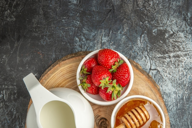 Fragole fresche di vista superiore con miele e pane sulla gelatina dolce della frutta dell'alimento di superficie scura