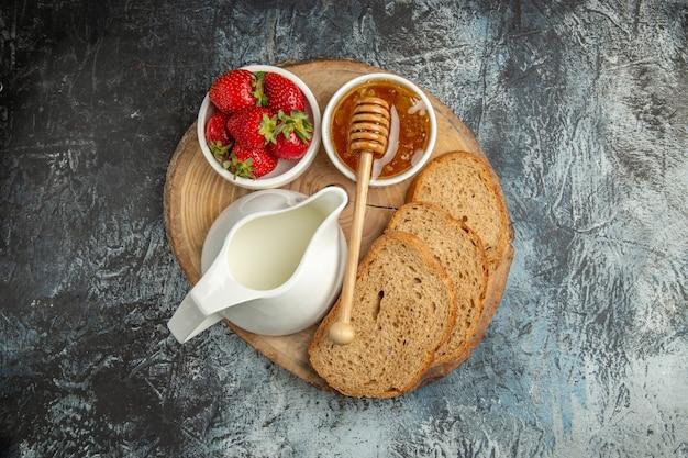 Vista dall'alto fragole fresche con miele e pane su una gelatina dolce di frutta superficie scura