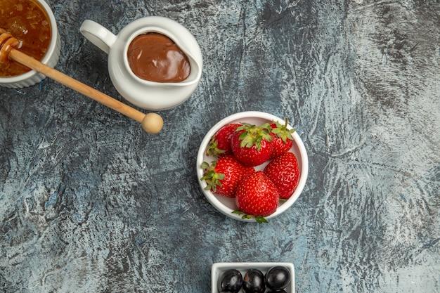 Vista dall'alto fragole fresche con olive e miele sulla bacca di frutta dolce superficie scura