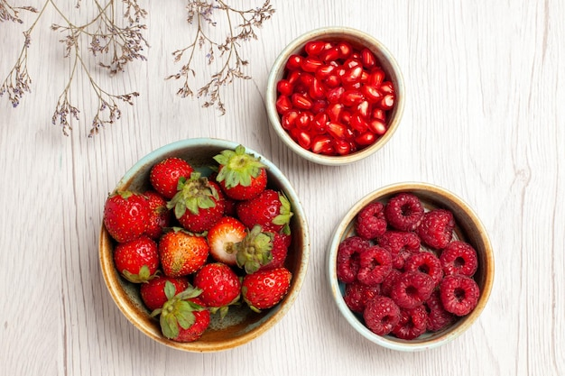 Top view fresh strawberries with raspberries and pomegranates on white desk berry fresh fruit mellow ripe wild
