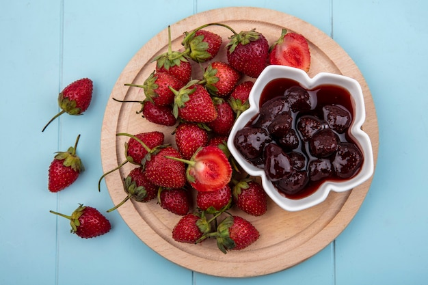 Top view of fresh strawberries with a strawberry jam on a bowl on a wooden kitchen board on a blue background