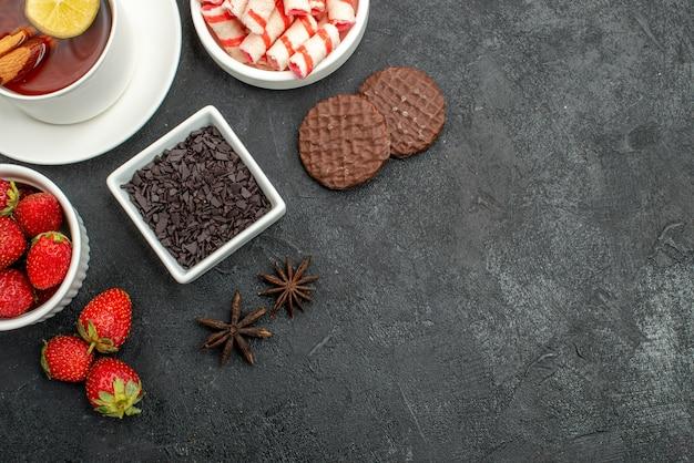 Вид сверху свежей клубники со сладостями и чаем