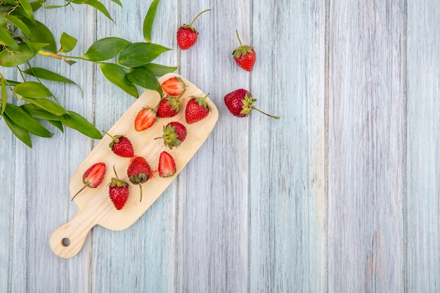 Top view of fresh strawberries on a wooden kitchen board with leaves on a grey wooden background with copy space