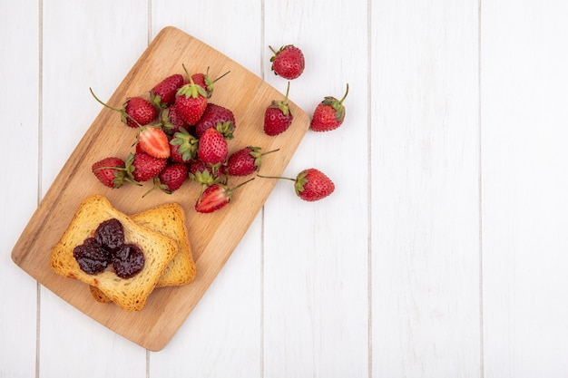 Top view of fresh strawberries on a wooden kitchen board with toasted bread on a white wooden background with copy space