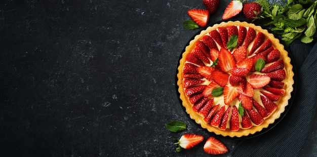 Top view of fresh strawberry flan cake on black background