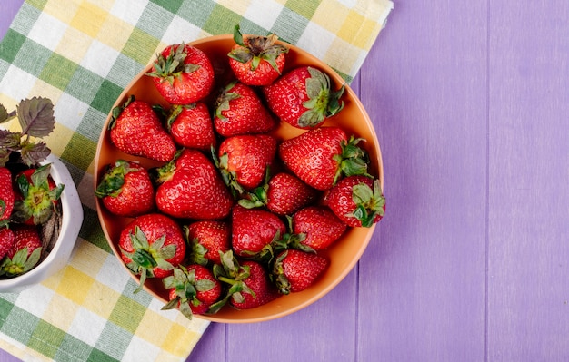 紫色の背景に皿の上から見る新鮮なイチゴ