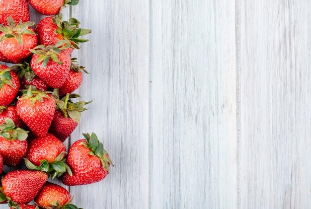 白い木製の背景にコピースペースを持つ左側のトップビュー新鮮なイチゴ