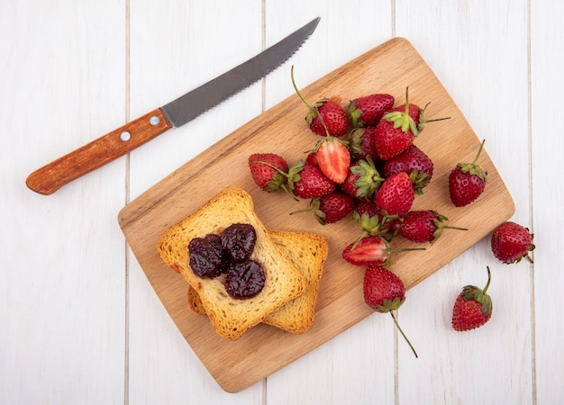 Top view of fresh strawberry with toasted bread on a wooden kitchen board with knife on a white background
