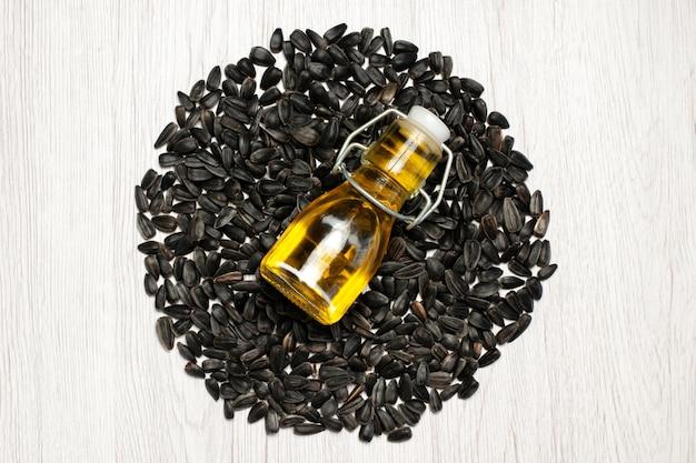 Vista dall'alto semi di girasole freschi semi di colore nero su bianco scrivania foto olio snack molti semi