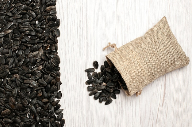 Vista dall'alto semi di girasole freschi semi di colore nero su superficie bianca semi di semi snack foto molti olio