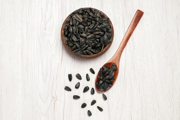 흰색 책상에 있는 신선한 해바라기 씨앗 검은 씨앗 많은 기름 식물 가방 씨앗 상위 뷰