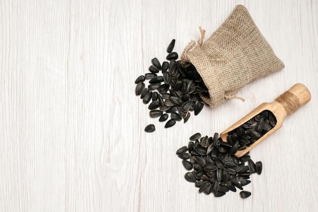 흰색 책상 위에 있는 신선한 해바라기 씨앗 검은 씨앗 많은 종자 기름 식물 가방