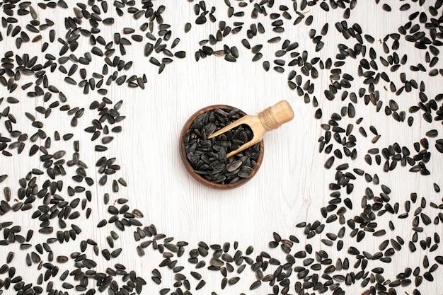 Vista dall'alto semi di girasole freschi semi neri su superficie bianca semi di mais snack olio molte foto
