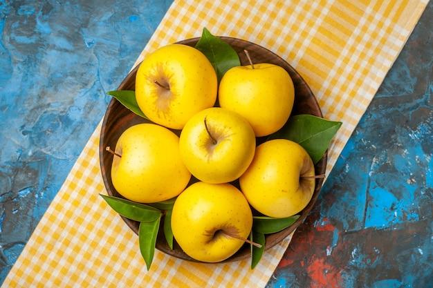 青い背景の上のプレート内の新鮮な甘いリンゴの上面図