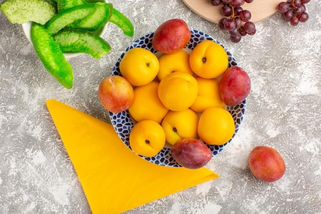 Вид сверху свежие сладкие абрикосы, желтые фрукты внутри тарелки со сливами и виноградом на белом столе