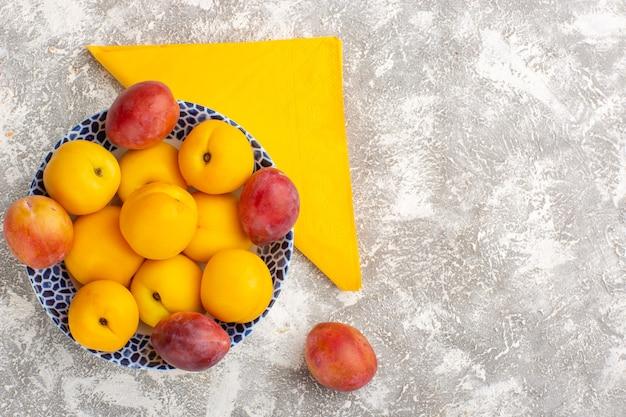 Вид сверху свежих сладких абрикосов, желтых фруктов внутри тарелки со сливами на белой поверхности
