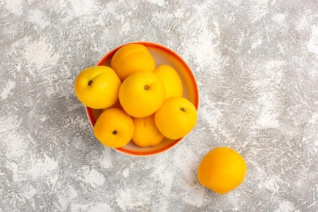 Вид сверху свежие сладкие абрикосы желтые фрукты на белой поверхности